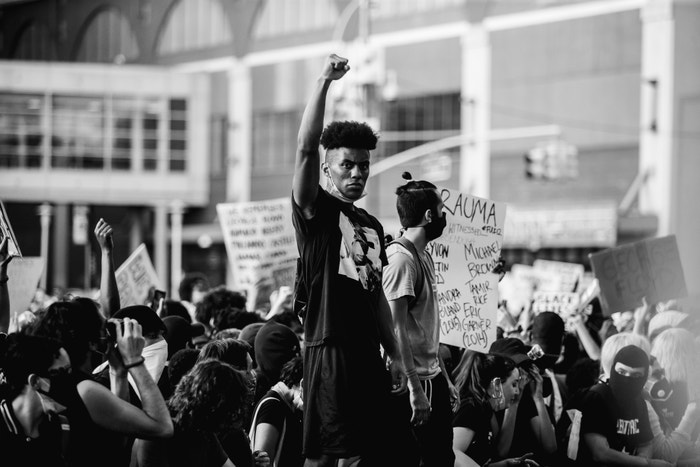 30 May 2020. A young black man raises his fist to show solidarity with the other black protesters in the protest at the Barclays Center, Brooklyn, New York.