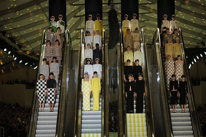 Chris Moore's career charts the change in fashion presentations from intimate gatherings in fashion salons in the 1950s to the sleek theatre and high production values of contemporary fashion, such as this show for Louis Vuitton, Spring/Summer 2013.