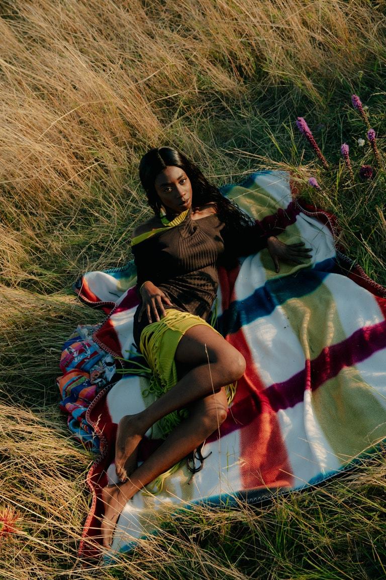 Ace Tee (raperka); šaty, PREEN by THORNTON BREGAZZI; boty, FENDI; náušnice, MALAIKA RAISS; deka, HERMÈS.