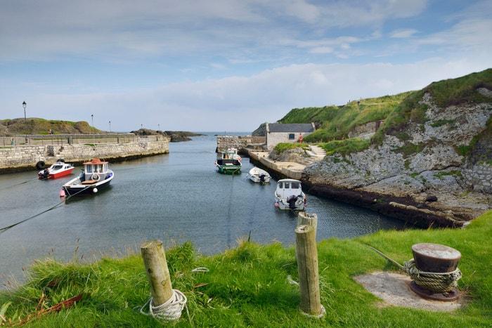 Ballintoy, hrabství Antrim, Severní Irsko: Rybářská vesnice Ballintoy, nedaleko od Giant's Causeway (Obrův chodník), se ve druhé řadě, kdy se Theon Greyjoy vrací domů na Železné ostrovy, promění v Pyke. Přístav má dokonce pamětní desku, která natáčení Hry o trůny připomíná. Autor: Andia/UIG via Getty Images