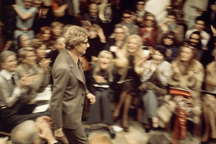 "Yves Saint Laurent, Spring/Summer 1974, Paris. During these earlier years of fashion shows, there was no podium for photographers. ""We all had to put ourselves where we could and I stood perched on the windowsill of the salon – it was a great position to see Yves' front row going wild for him in the finale,"" Chris Moore remembers."