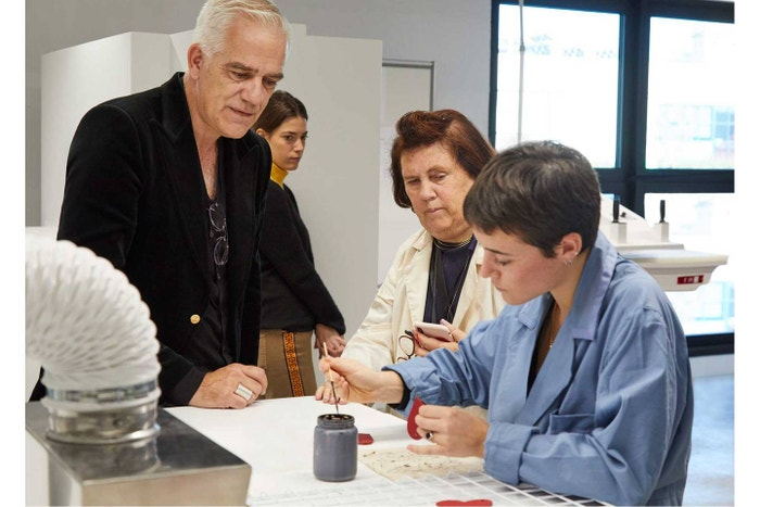 Massimo Rigucci and Suzy watch a young student of Gucci's Scuola dei Mestieri practice her craft.
